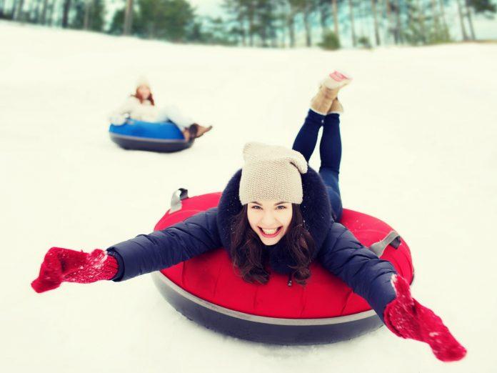 girl sliding down hill on inner tube