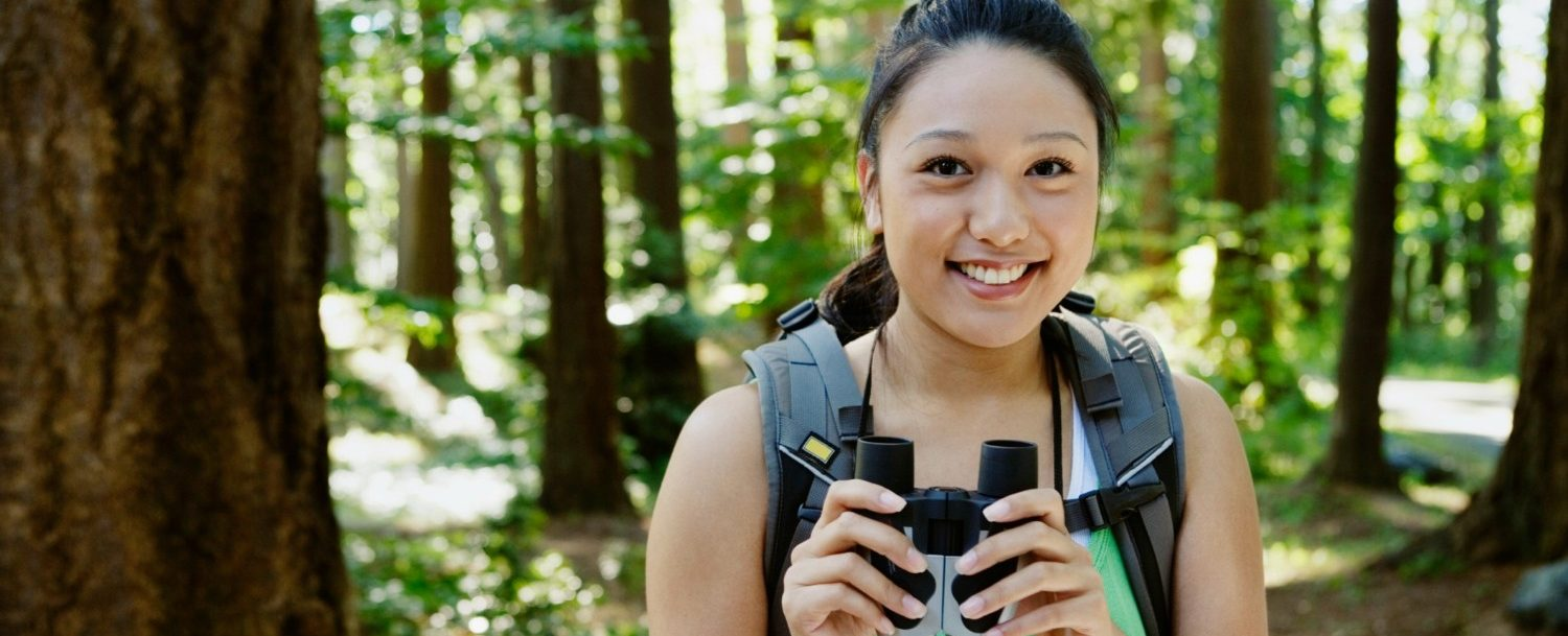 woman holding a pair of binoculars in the woods