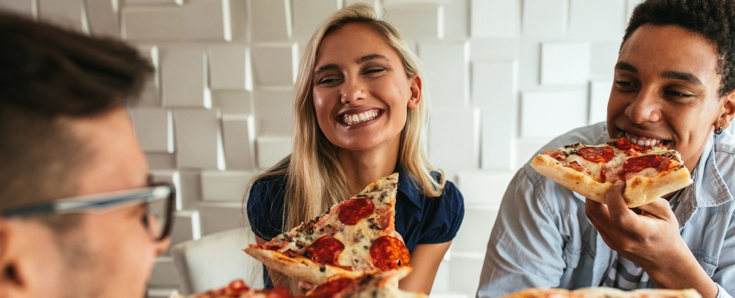 three people eating pizza