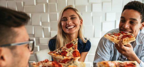 three people eating pizza